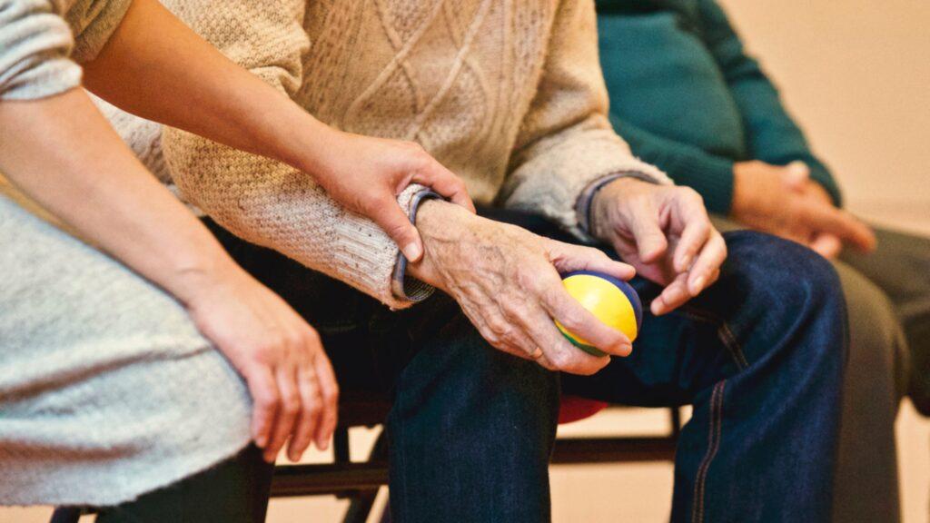 Muistihoitaja ja muistisairas ihminen  harjoittelevat hienomotoriikkaa pallolla.