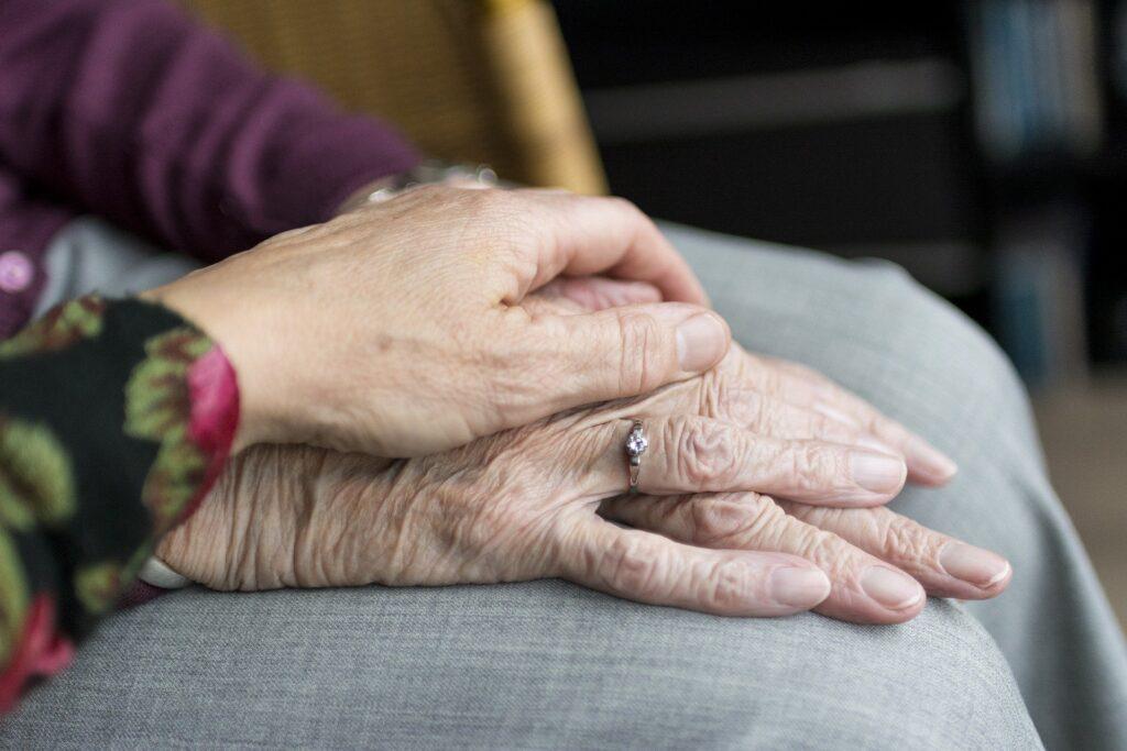 Käsi koskettaa vanhan ihmisen käsiä.