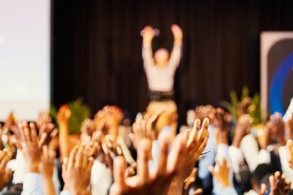 Innokkaita opiskelijoita kädet ilmassa.